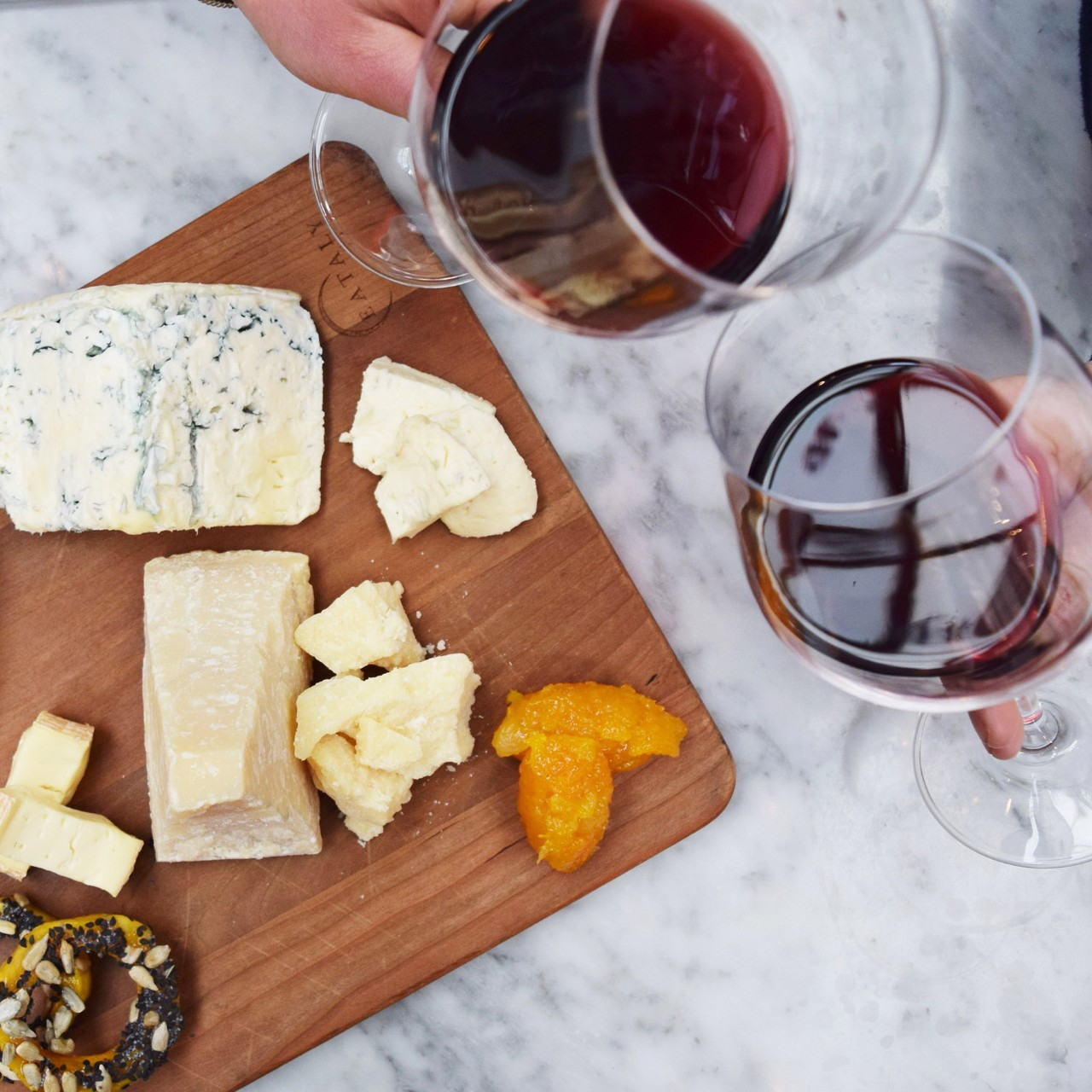 Patrons clink wine glasses and enjoy a cheeseboard at Eataly World Trade Center